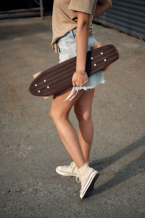 Young Woman With Longboard. Girl skater posing on longboard in sunny weather