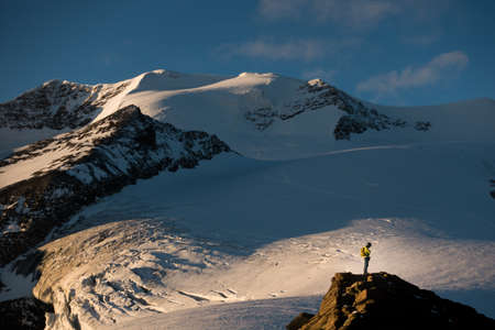 Reflexive climber alone in alpine enviroment under the Castor summit, near Quintino Sella, Italian Alps.