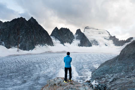 A reflexive mountaineer looking a glacier, Ecrins National Park, French Alps