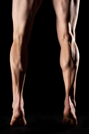 Studio photography of the legs and the calf muscle of a fibrous cyclist athlete with black background Stock Photo