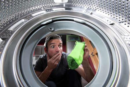 Worried caucasian man taking out a colorful sock from the drum of the washing machine. Interior view.