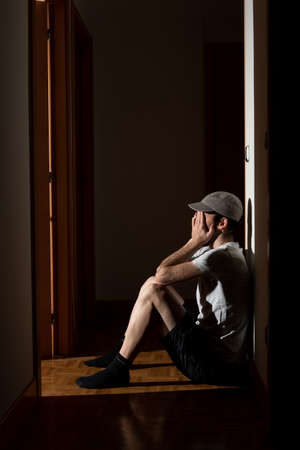 Mental health concept. Depressive man sat alone on the floor of the corridor of his house crying, hands covering his face. Psycological trauma.