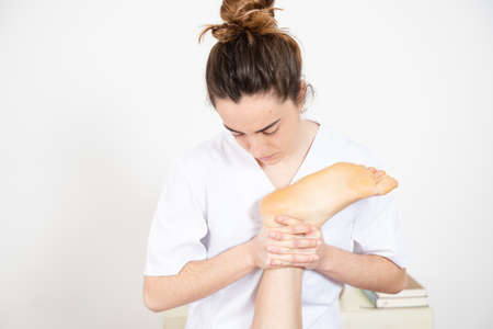 Physiotherapist working on the leg muscles and articulations of a patient.