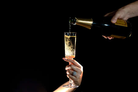Close up of man and woman hands celebrating Valentines Day with champagne. . High quality photo