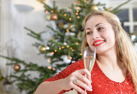 girl on a couch beside the christmas-tree holding a glas of champagne