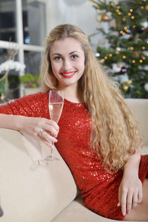 new year girl smiling on a couch beside the christmas-tree holding glass of champagne Stock Photo