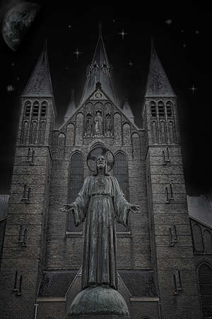 stone sculpture in front of church in the Netherlands during evening Stock Photo