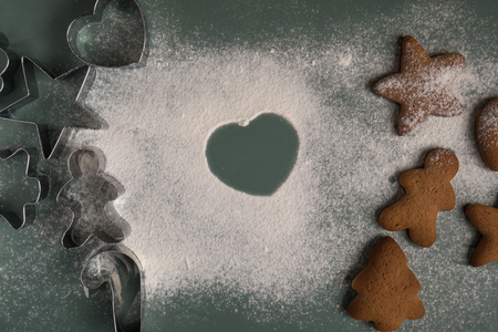 Cooking gingerbread cookies from dough using different forms - heart, star, Christmas tree, men,  on a wooden saw with Christmas tree branches. Home baking. Preparing for christmas concept. Stock Photo