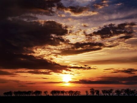 Natural Sunset Over Field. Bright Dramatic Sky And Dark Ground. Countryside Landscape Under Scenic Colorful Sky At Sunset.