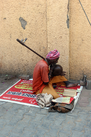 march 17: Vrindavan, India - March 17, 2013 - A street musician in traditional dress playing sitting on a newspaper in March 17, 2013, in Vrindavan, India. Editorial