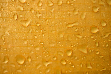 yellow waterproof material, rip stop cloth with drops of water background