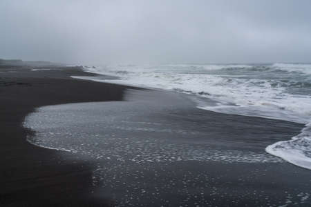 Black volcanic sand at Khalaktyrsky beach of the Pacific at Kamchatka peninsula, near Petropavlovsk-Kamchatsky, Russia