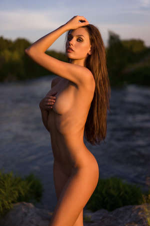 naked girl posing on nature at sunset