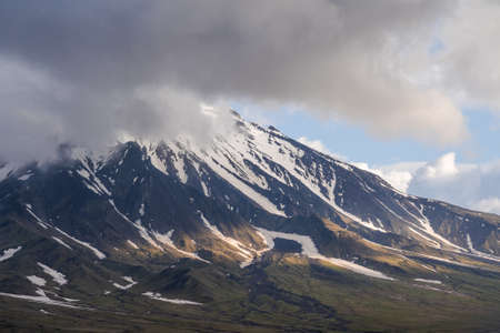 Beautiful autumn volcanic landscape - view of snow-capped cone of stratovolcano Bolshaya Udina Volcano in Klyuchevskaya Group of Volcanoes. Russian Far East, Kamchatka Peninsula, Eurasia.