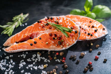 Fresh salmon with spices and lemon on wooden table. Standard-Bild - 130773297