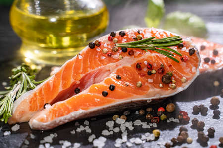 Fresh salmon with spices and lemon on wooden table. Standard-Bild - 130773301