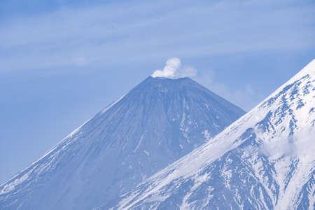 Nature of Kamchatka - beautiful volcanic landscape: view on Kamen Volcano, active Klyuchevskoy Volcano and active Bezymianny Volcano. Russian Far East, Kamchatka, Klyuchevskaya Group of Volcanoes. Standard-Bild - 130773449