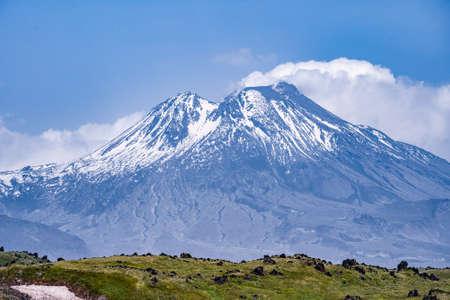 Natur Kamtschatkas - schöne Vulkanlandschaft: Blick auf den Vulkan Kamen, den aktiven Vulkan Klyuchevskoy und den aktiven Vulkan Bezymianny. Russischer Ferner Osten, Kamtschatka, Kljutschewskaja-Vulkangruppe. Standard-Bild