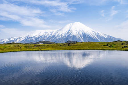 Volcano and lake with reflection in water in Russia on Kamchatka. Stock fotó