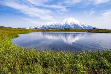 Volcano and lake with reflection in water in Russia on Kamchatka.