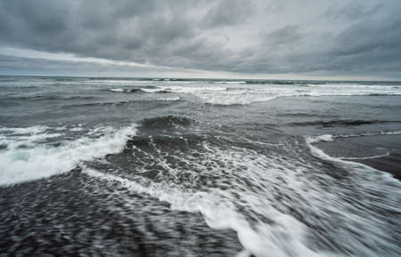 The coast of the Pacific Ocean on the Kamchatka Peninsula, Russia. Sea waves rolls on the stretching black volcanic sand beach. Nature, travel and adventure concept. Imagens