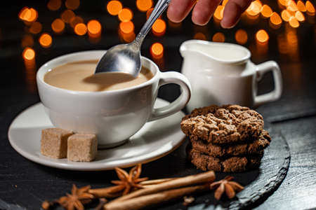 hands holding coffee cookies and spices on wooden rustic background. Imagens