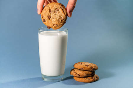 hands holding cookies with milk on blue color background. Imagens