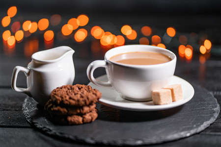 Chocolate cookies, coffee, spices on a background of Christmas lights. Christmas cozy evening concept Imagens