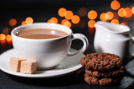 Chocolate cookies, coffee, spices on a background of Christmas lights. Christmas cozy evening concept Фото со стока