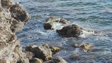Large stones on background splashing sea waves. Ocean waves breaking with splashes on wet rocks on beach. Stony coast and transparent sea background