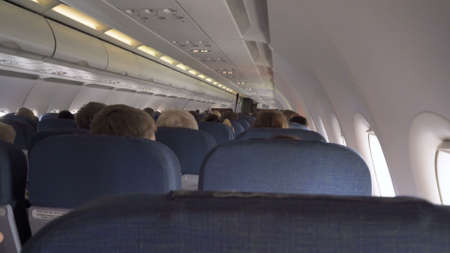 Interior passengers airplane with people on seats. Aircraft cabin with rows of seats. Passengers traveling by a modern commercial plane, inside of an airplane. Travel concept. Imagens