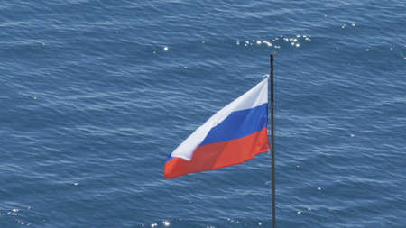 Russian flag on the background of the sea. Russian tricolor on a background of blue water Imagens