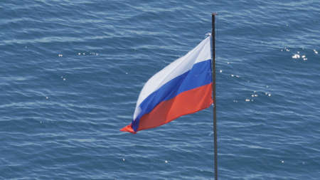 Russian flag waving in the background of the glare on the water. Stern of the ship.