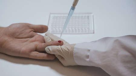 Lab technician pours blood samples into test tubes Imagens