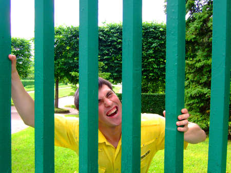waiting convict: Photo of the young man behind a green fence. Stock Photo