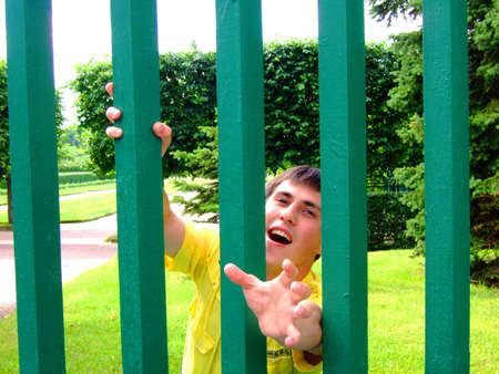 waiting convict: Photo of the young man behind a fence. Stock Photo