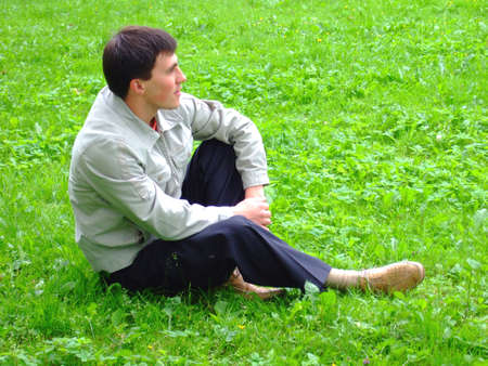 Photo of the thoughtful young man on a grass. photo
