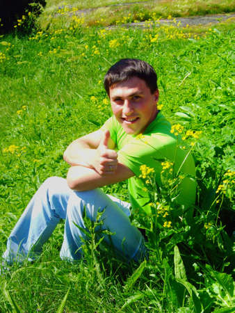 The young man on a grass, shows the big finger. photo