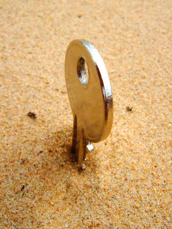 Photo of a key in sand in vertical position. photo