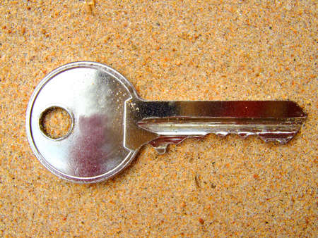 Photo of a key which lays on sand. photo