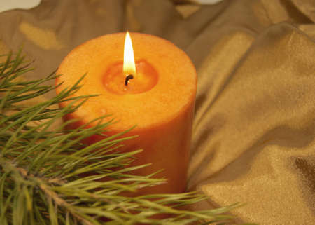 tissu or: Burning candle on a background of a gold cloth with a branch of a green fur-tree.