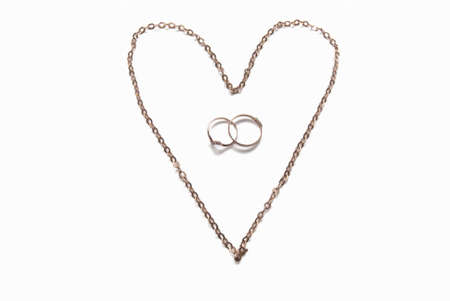 shackled: Photo of heart laid out from a gold chain and wedding rings.