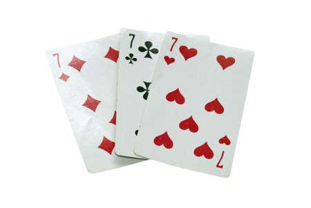 Foto di tre vecchie carte da gioco, tre sette. Archivio Fotografico - 4203037