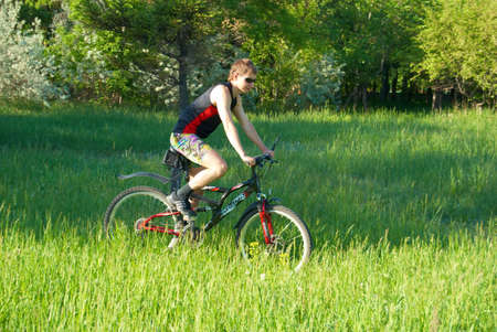 The bicyclist on a bicycle close up on the nature. Stock Photo