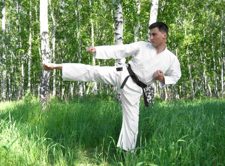 The karateka on a background of a wood. photo