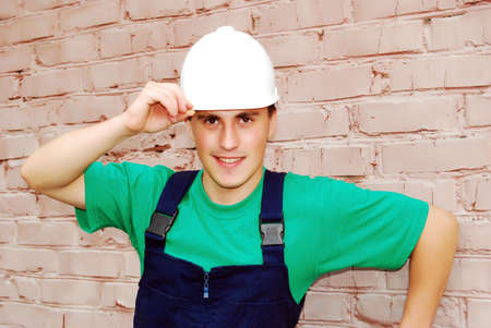 Muscular young man in a builder uniform. Stock Photo - 6174529