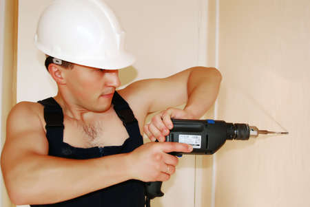 Muscular young man in a builder uniform.