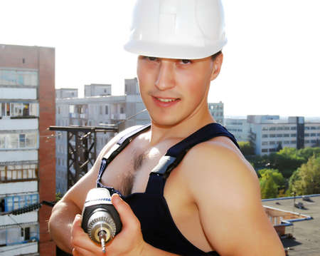 Muscular young man in a builder uniform. photo