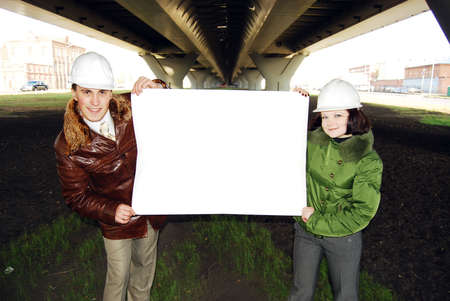 Young architects wearing a protective helmet standing. photo