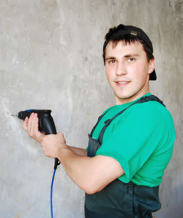 Muscular young man in a builder uniform. Stock Photo - 8038059